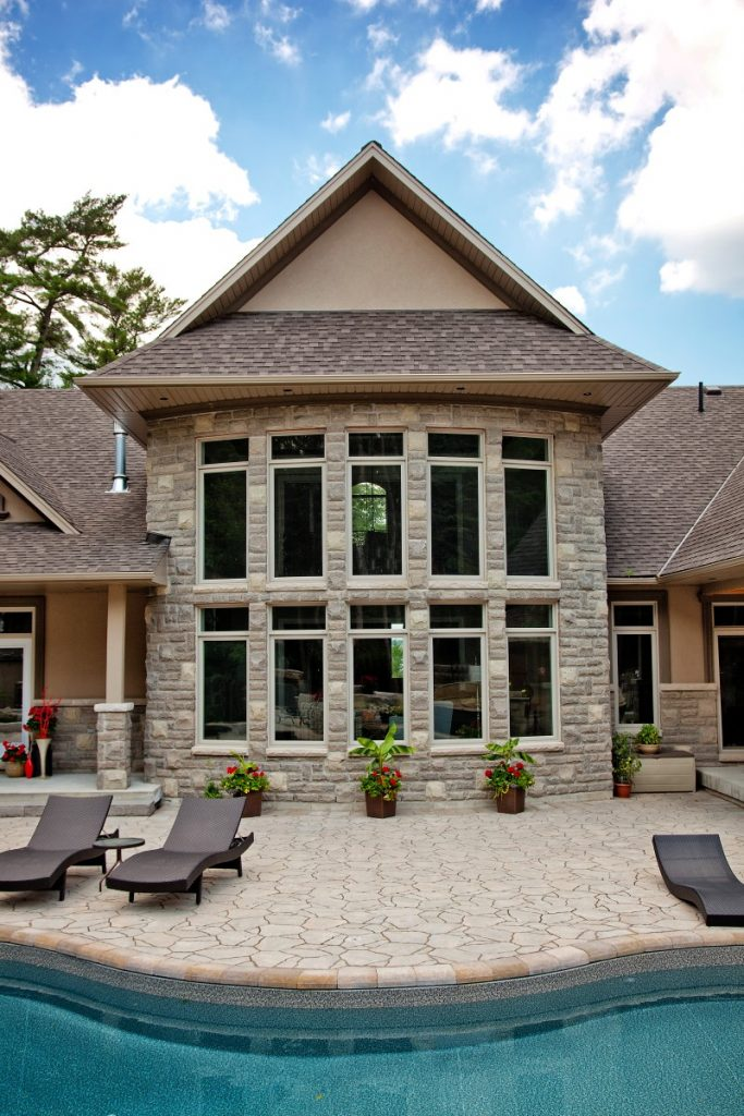 exterior of home with two levels of casement windows overlooking a pool